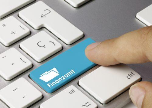 mann drückt auf tastatur zur datenübermittlung ans finanzamt