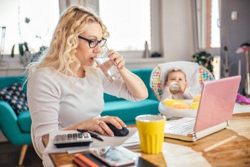 Mutter trinkt Wasser vor dem Laptop