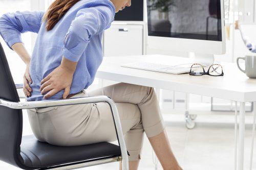 Frau mit Rückenschmerzen am PC