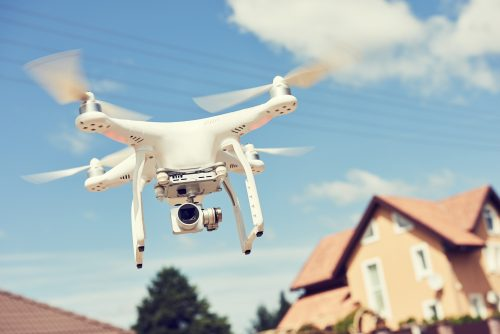 Drohne fliegt, Häuser im Hintergrund