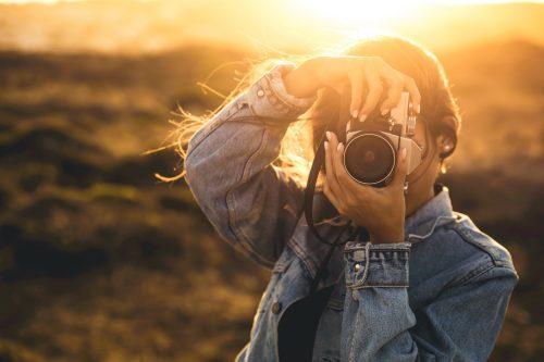 Frau hält Fotoapparat draußen