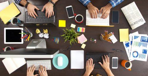 mehrere Personen arbeiten am PC oder laptopn an einem schreibtisch