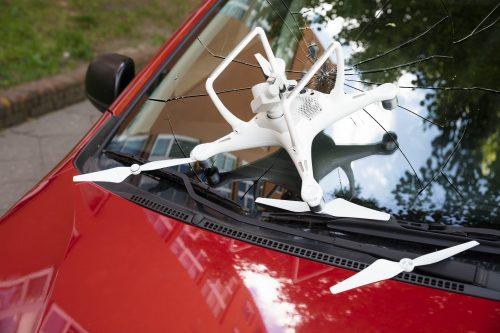 Kaputte Drohne auf zerstörter Autofrontscheibe