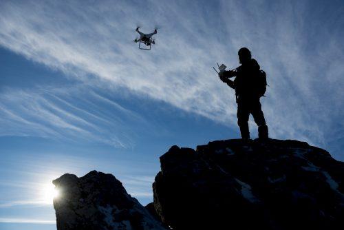 Person fliegt Drohne auf Berg