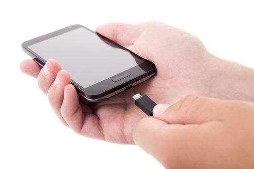 Hände halten Handy und USB Kabel
