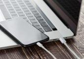 Handy liegt auf Laptop, beide mit USB-Kabel verbunden