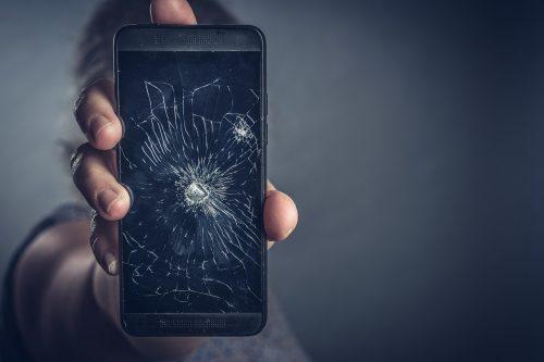Zerstörtes Handy wird in Hand gehalten