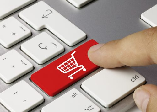 Finger tippt Tastaturtaste mit Einkaufswagen