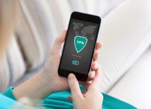 Frau hält smartphone mit sicherheitsanwendung in der hand