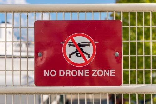 Schild mit Drohnenverbotszone an Zaun