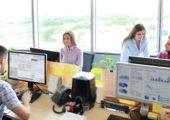 Geschäftspersonen sitzen und stehen an Computern