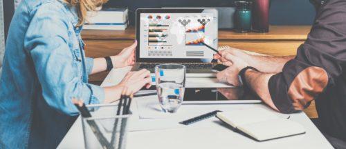 Zwei Personen sitzen vor Laptop mit Diagrammen