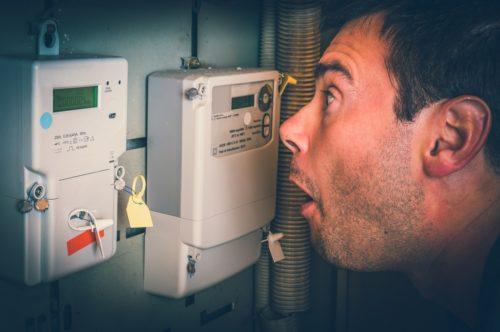Bedeutung Mann schaut schockiert auf Stromzähler