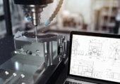 CNC-Fräse arbeitet neben Laptop mit CAD-Zeichnung