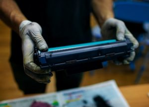 Blaue Kartusche eines Laserdruckers wird nach Test ausgetauscht