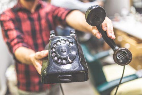 Mann mit altem Wählscheiben-Telefon