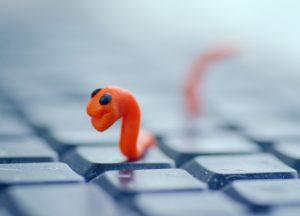Schadsoftware: Plastikwurm auf Tastatur