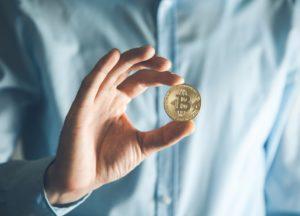 Bitcoins einfach erklärt: Mann hält Bitcoin zwischen den Fingern