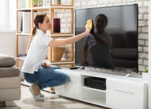 Frau putzt Fernseher